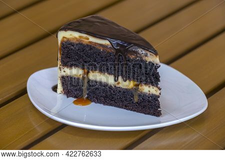 Slice Of Caramel Chocolate Cheese Cake On White Plate