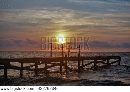 Dawn Over The Caribbean Sea. The Sun Shines Through The Clouds. A Sky Of Orange Hues. A Wooden Footp
