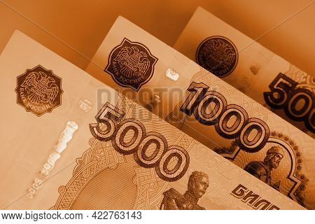 Russian Banknotes 5000, 1000 And 500 Rubles Close Up. Brown Tinted Wallpaper, Background Or Backdrop
