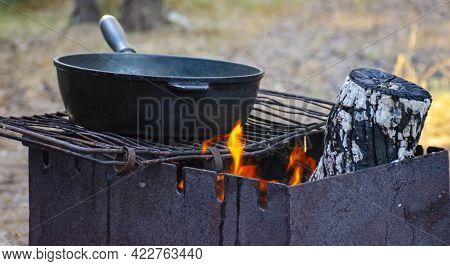 Fry Food In Old Iron Pan Over The Fire. Selected Focus On The Grill And On The Pan. Cast Iron Frying