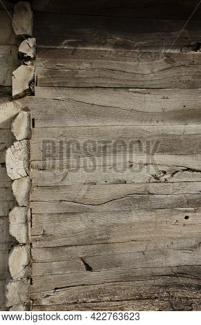 Corner Of An Old Wooden House In Country Side With Round Logs. Old Wood Planks. Gray Rustic Wooden T