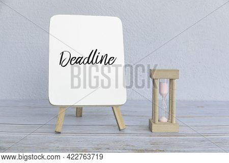 Concept Of Deadline And Time With Sand Clock And White Board Written With Deadline.