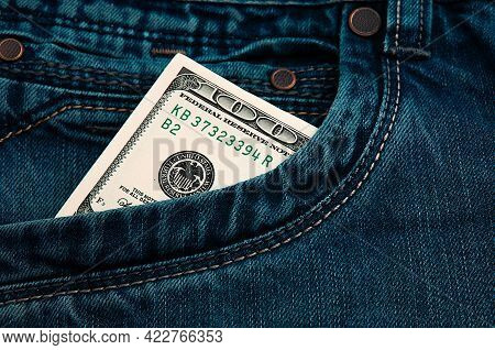 A Hundred-dollar Bill In The Pocket Of His Jeans. The One Hundred American Dollar Bill Is Sticking O