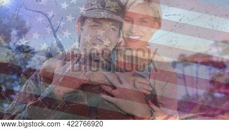 Composition of female soldier embracing smiling wife over american flag. soldier returning home to family concept digitally generated image.