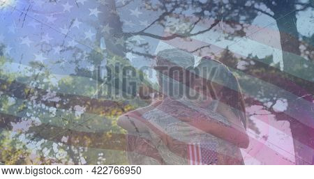 Composition of male soldier embracing smiling daughter over american flag. soldier returning home to family concept digitally generated image.