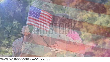 Composition of male soldier embracing daughter over american flag. soldier returning home to family concept digitally generated image.