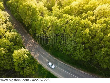 White Car on Highway road in summer time nature from air in the forest. View from a drone. Aerial view.