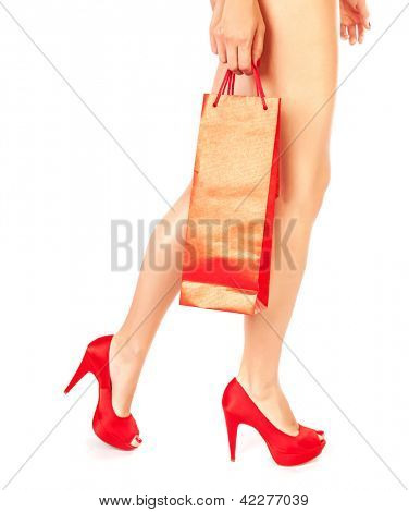 Picture of slim female with red shopping bag in hand wearing luxury shoes on high heels, naked woman's legs dressed in fashionable footwear isolated on white background, money spending concept