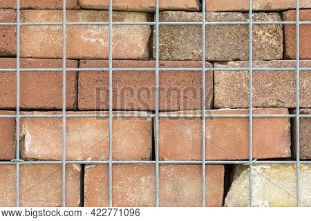 Fragment Of A Brick Wall With A Metal Mesh. Texture, Wall, Stone Texture, Metal Mesh, Fence. Red Cla