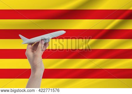 Airplane In Hand With National Flag Of Catalonia. Travel To Catalonia.