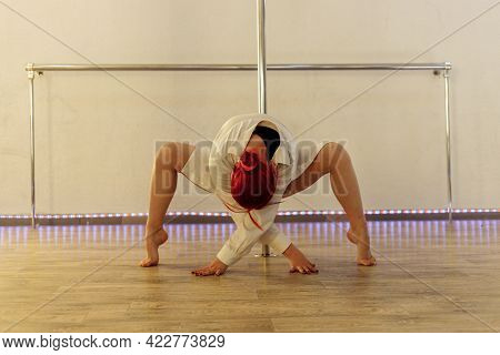 Atttractive Woman On Pole-dancing Workout In Class. Sexy Lady On Pole-dancing Training In Class.