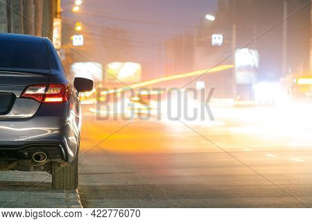 Close Up Of Parked Car On Roadside At Night With Blurred View Of Traffic Lights Of Moving Vehicles O