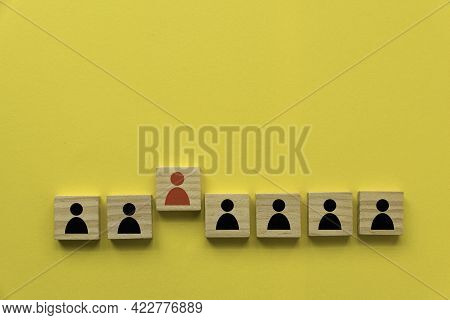 A Row Of Wooden Cube With People Icon With One Red People Standing Out From Other.