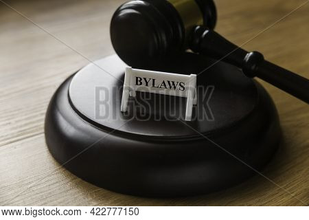 Bylaws Phrase With Gavel On Wooden Background. Business And Law Concept