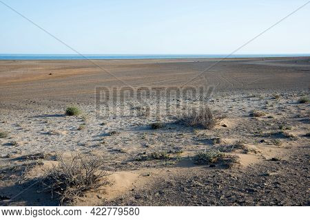 Arid Landscape With Dry Soil At Lanzarote, Canary Islands, Spain. Blue Ocean In The Distance.