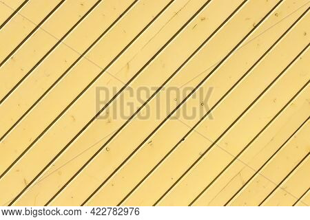 Texture Of An Edge Siding Wall Made Of Painted In Yellow Panels With Multiple Knots As A Background