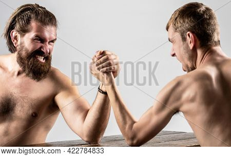 Heavily Muscled Bearded Man Arm Wrestling A Puny Weak Man. Arms Wrestling Thin Hand, Big Strong Arm