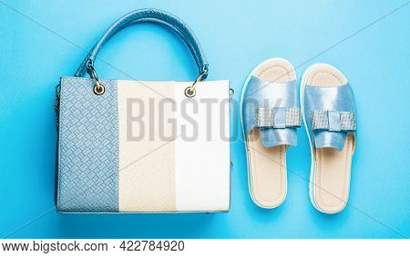 Slippers On A Blue Background. Slippers For The Summer. Ladies Bag And Stylish Blue Shoes. Stylish B