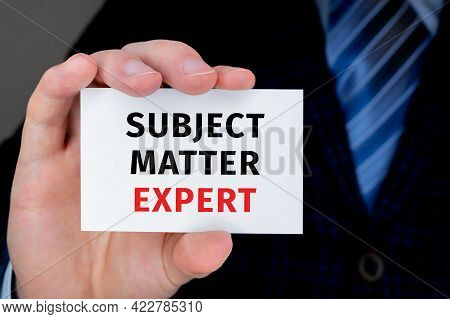 Closeup On Businessman Holding A Card With Subject Matter Expert Message, Business Concept Image Wit