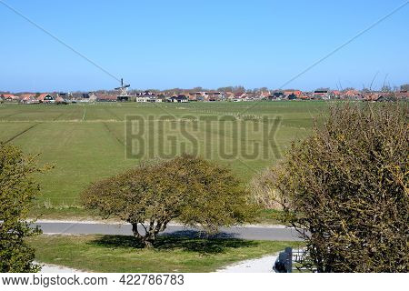 Typical Dutch Picture Overlooking Meadow And The Old Dutch Village Of Hollum, Ameland With A Windmil
