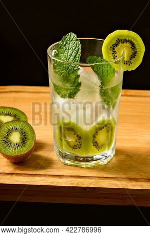 Iced Cocktail Glass Decorated With Kiwi And Mint With A Kiwi 2 Kiwi Halves Next To The Glass On A Wo