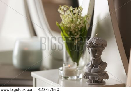 Beautiful David Bust Candle And Flowers On Table Indoors, Space For Text