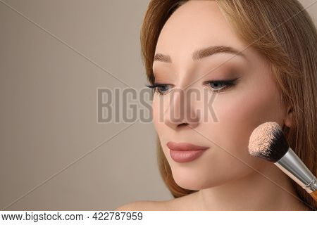 Beautiful Young Woman Applying Face Powder With Brush On Grey Background, Closeup. Space For Text