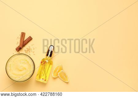 Body Scrub In Glass Jar, Oil, Lemon And Cinnamon On Yellow Background, Flat Lay. Space For Text