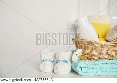 Baby Booties And Accessories On White Table Against Light Background. Space For Text
