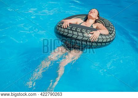 Happy Young Woman With Inflatable Ring Relaxing And Enjoying Summer In Swimming Pool
