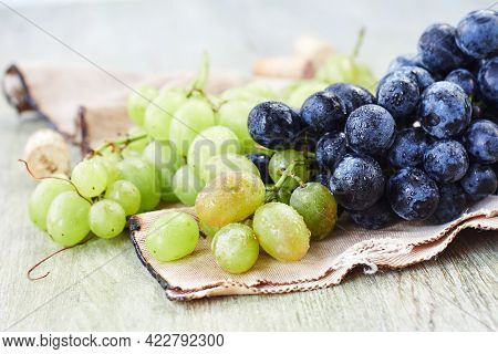 Bunch Of White And Blue Grapes On A Green Wooden Background.