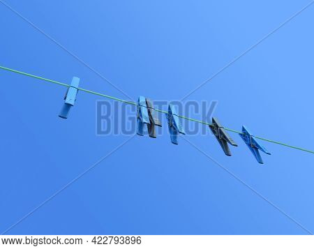Bottom View Of Clothespins Under Blue Sky. Laundry Line With Clothespins Hanging On The Rope. Colorf