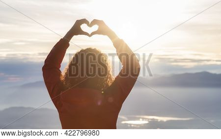 Adventurous Caucasian Adult Woman Hiking In Canadian Nature With Heart Shape Hands Over Looking Land
