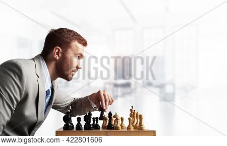 Businessman Moving Chess Figure In Chessboard. Successful Management And Leadership Concept. Handsom