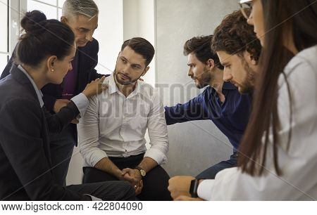 Group Of People Sitting In A Circle Supporting And Comforting A Sad Upset Young Man