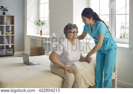 Smiling Caring Nurse Supporting Patient Assisting Senior Woman Get Up From Bed