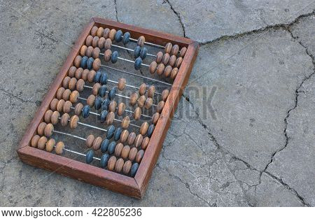The Old Abacus Is Located On Asphalt With Deep Cracks And Moss. Top View. Traditional Business Conce