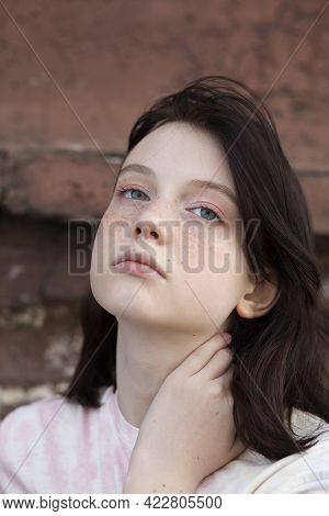 Portrait Of A Teenage Girl With Freckles On Her Face, Against A Brick Wall Background In The City.