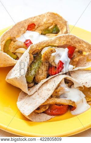 wholewheat  pitta bread filled with grilled chicken meat, jalapenos and red pepper