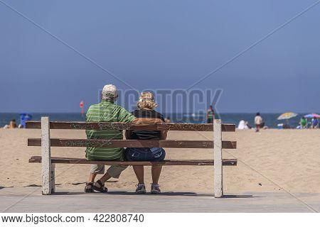Santa Monica, Ca, Usa - June 20, 2013:  Senior Couple Sitting On Boardwalk Bench Looking Over Sand B