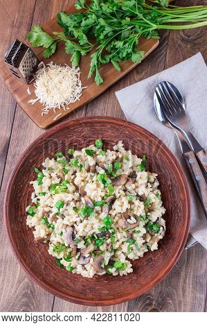 Mushroom Risotto With Arborio Rice, Brown Button Mushrooms And Green Peas, Garnished With Fresh Pars