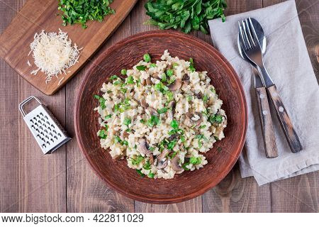 Risotto With Arborio Rice, Brown Button Mushrooms And Green Peas, Garnished With Fresh Parsley, Hori