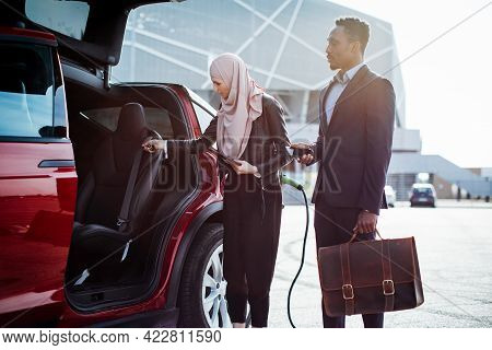 Muslim Female Dealer Showing Red Electric Car To African Male Customer Outdoors. African Man In Busi