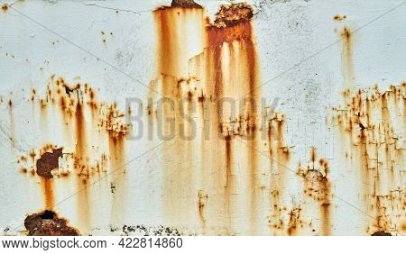 Patches Of Rust And Peeling Paint On A White Wall. Patches Of Rust And Rust Staining Are Mixed With