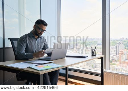 Indian Latin Focused Financier Sitting At Desk Doing Paperwork Working With Bank Taxes, Loans, Debit