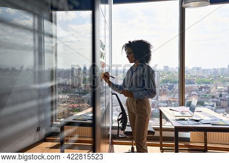 Young African American Executive Manager Businesswoman Writing Strategy Ideas On Sticky Notes On Whi