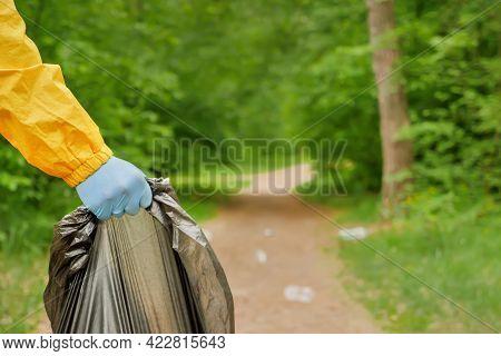 Volunteer Hands Picks Up A Plastic Trash Grass In Park. Eco Friendly Background Forest. Volunteer Cl