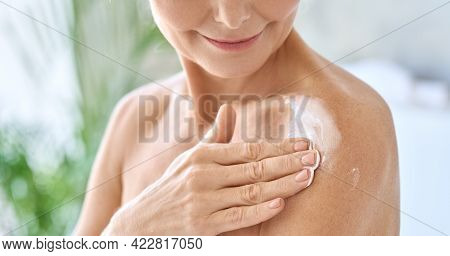 Naked Middle Aged 50s Woman Pampering Herself Doing Daily Routine Applying Nourishing Smoothing Body