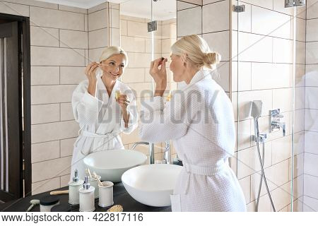 Senior Mature Older Caucasian Woman Applying Face Eye Contour Treatment With Antiaging Pipette Serum