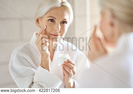 Attractive Mid Age Older Adult 50 Years Old Blonde Woman Wears Bathrobe In Bathroom Applying Nourish